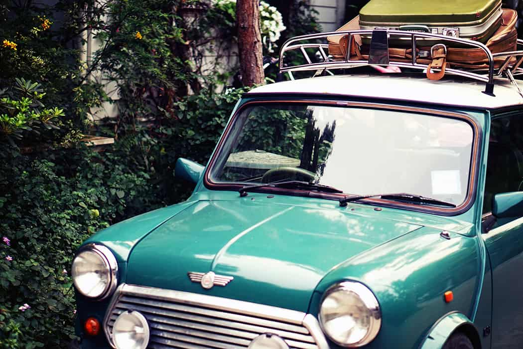 Classic green Mini Morris stacked with luggage